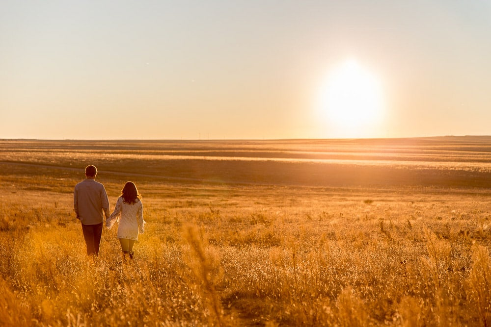 A couple holding hands and walking through a field at sunset during their outdoor engageent photo session In For Collins, Colorado.
