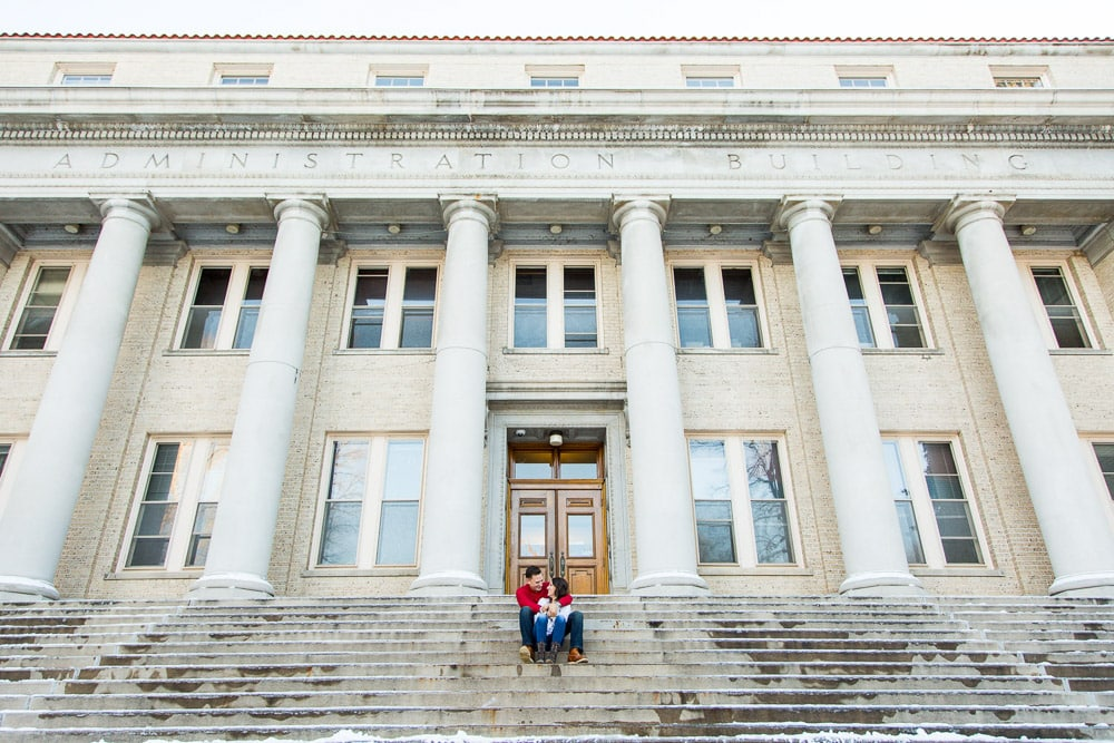 A couple sitting on the steps of the admin building at CSU during their winter engagement photo session in Fort Collins.