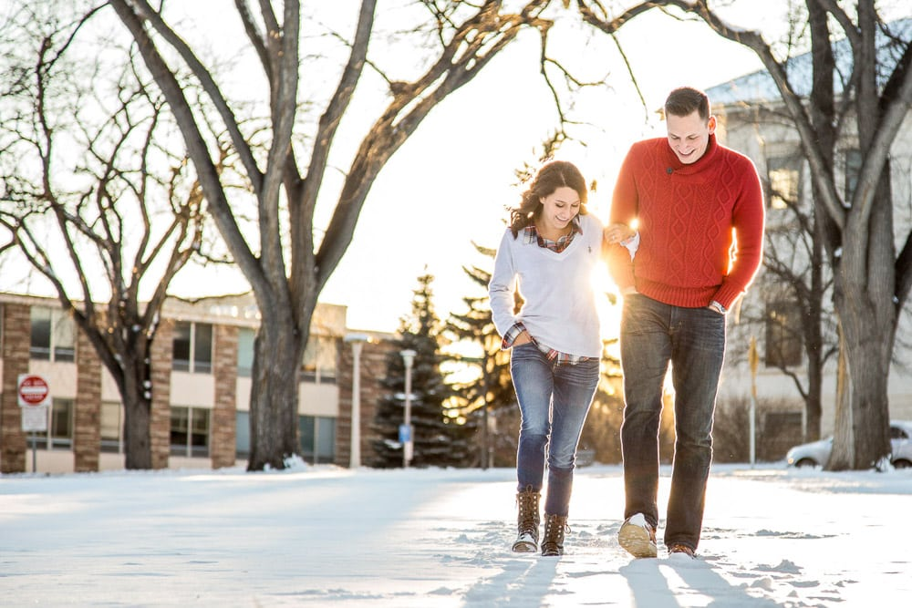 A young couple walking in the snow at the CSU oval during their Fort Collins winter engagement photo session.