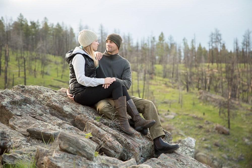 A couple sit on a rock in the mountains during their outdoor engagement photo session near Fort Collins, Colorado.