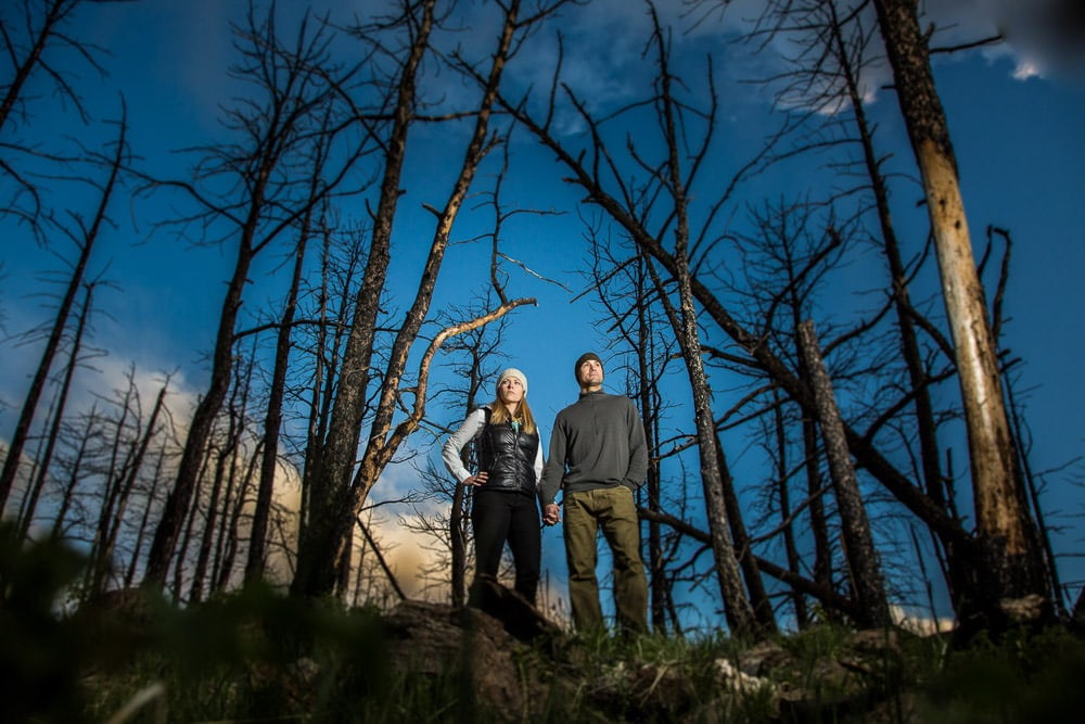 An outdoorsy couple stand among the trees during their mountain engagement photo session in Fort Collins, Colorado.