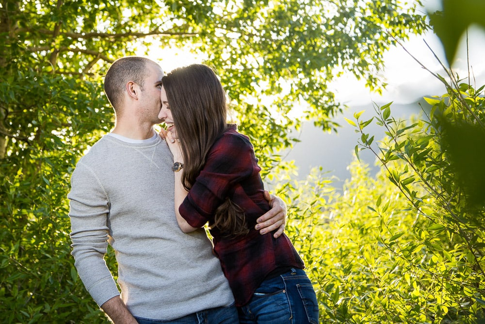 A guy whispering in his fiance's ear in the forest during their engagement photo session at Rocky Mountain NAtional Park.