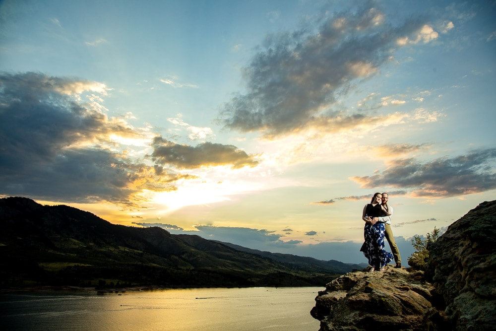 A couple standing on a cliff at sunset during their engagement photo session at Horsetooth Reservoir.