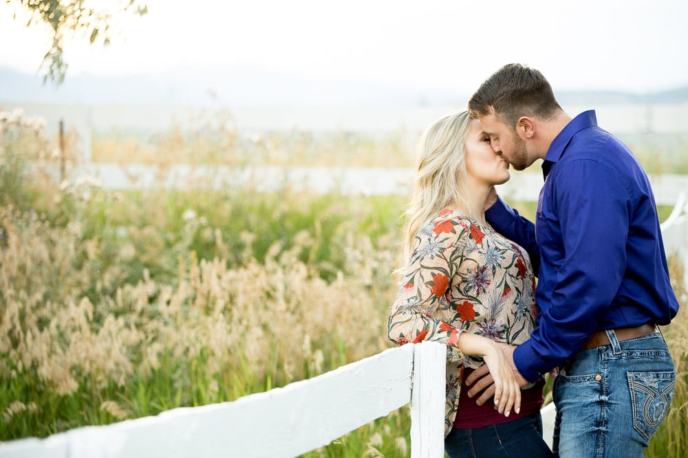 A couple leaning against a white fence kissing in a field at their outdoor Fort Collins engagement photo session.