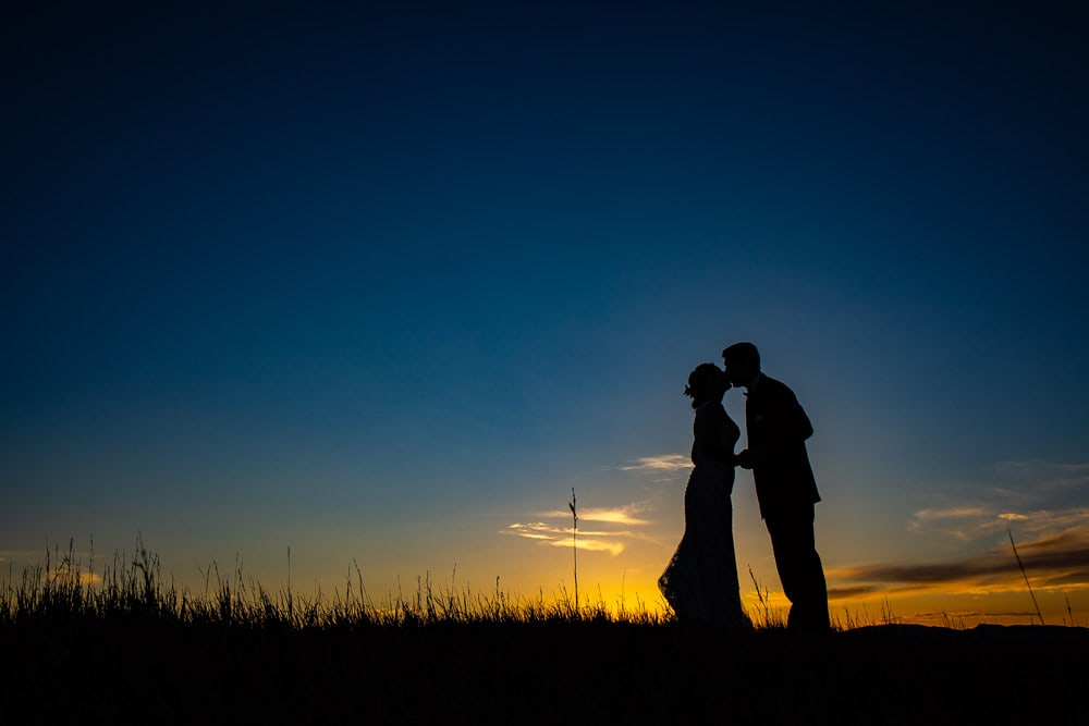 Silhouette of a brdie and groom kissing at sunset at their Big Red Barn wedding at Hiighland Meadows.
