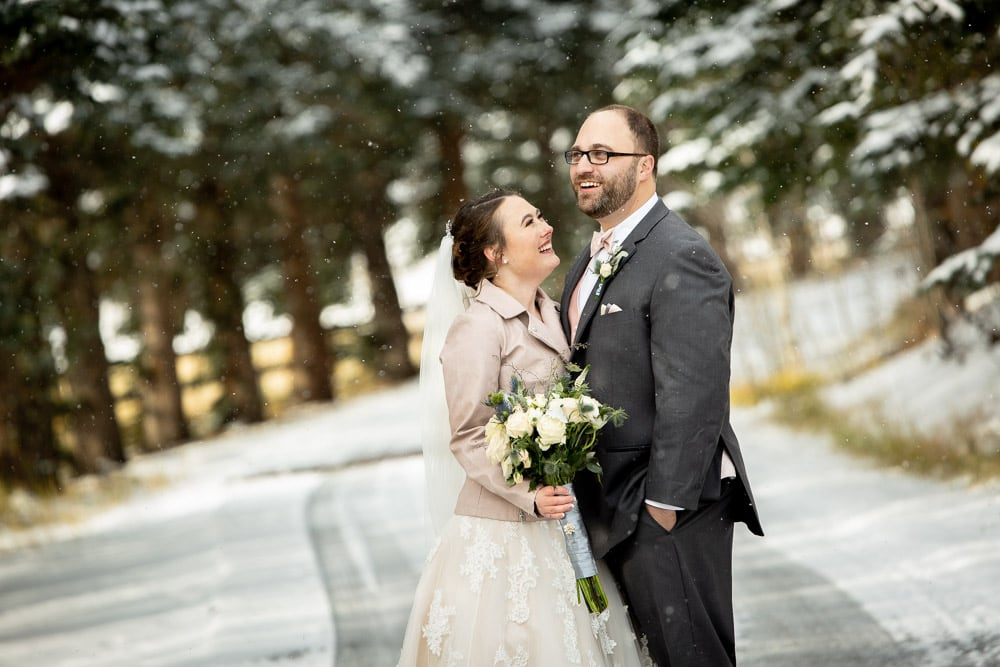 A bride and groom laughing in the snow at their winter wedding in the Colorado mountains.