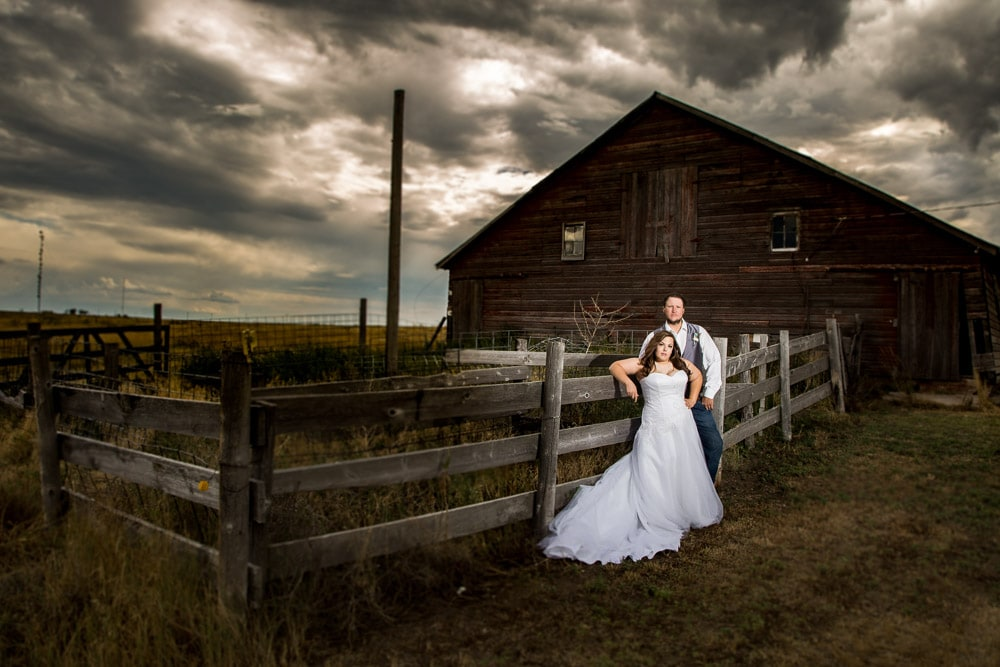 Dramatic photo of a bride and groom leaning on a fence in front of a barn at their rustic barn wedding near Fort Collins.