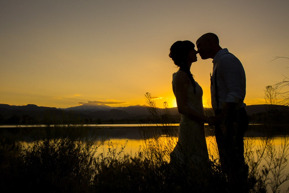 A silhouette of a bride and groom kissing at sunset near a lake after their DIY Fort Collins wedding.