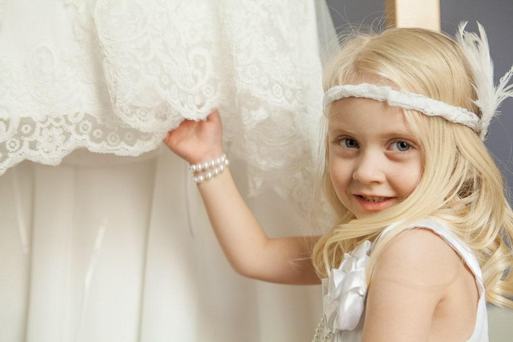 A flower girl in a vintage dress and headband stands near a wedding dress.
