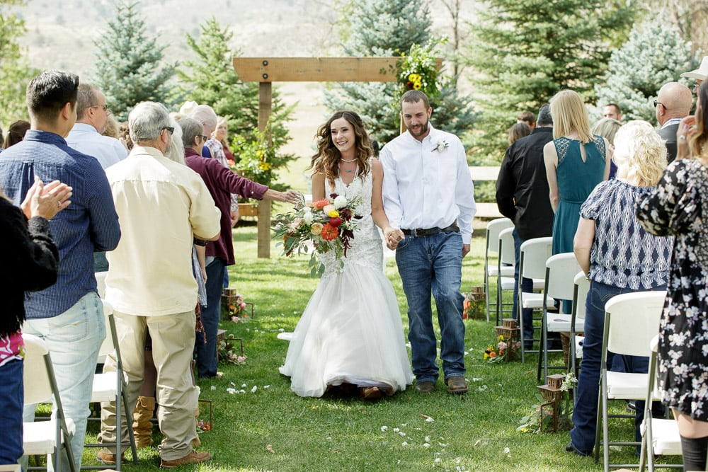 A bride and groom smile as they walk down the aisle after their bohemian wedding at the McC Ranch in Colorado.