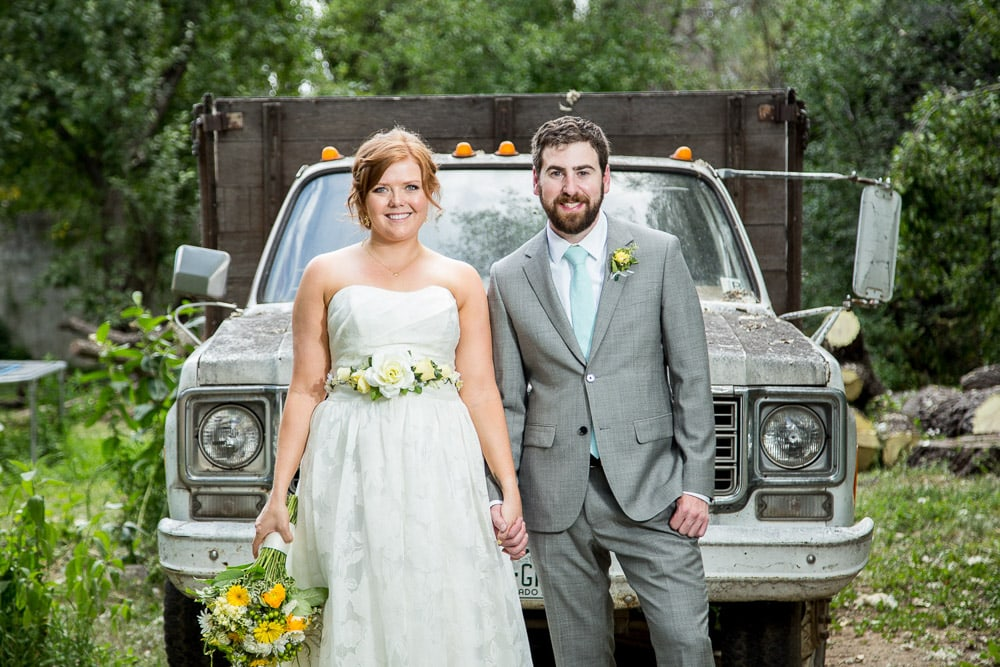 A bride and groom hold hands in front of an old truck at their DIY Happy Heart Farm wedding in Fort Collins.