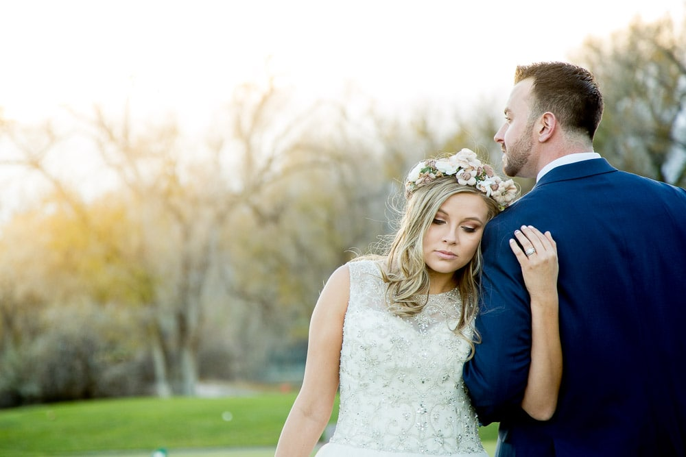A bohemian bride rests on her husbands shoulder at sunset during their Greeley Country Club wedding.
