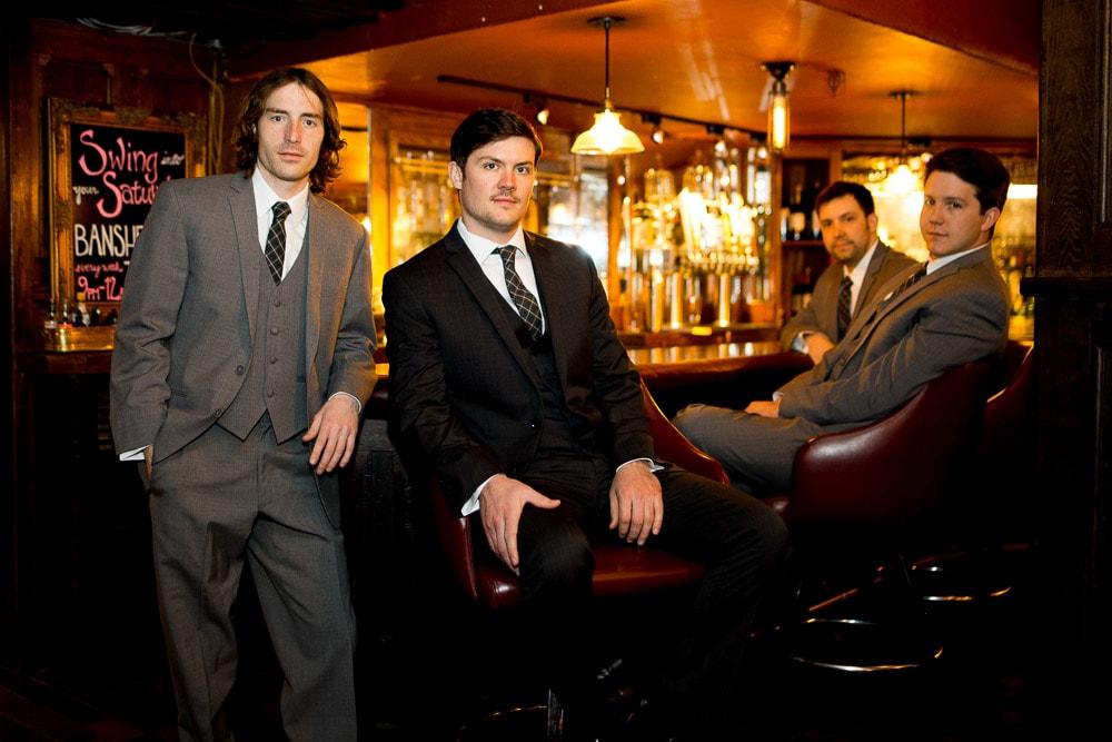 A grrom and groomsmen sit at a bar under the Hotel Boulderado before his modern Boulder, Colorado wedding.