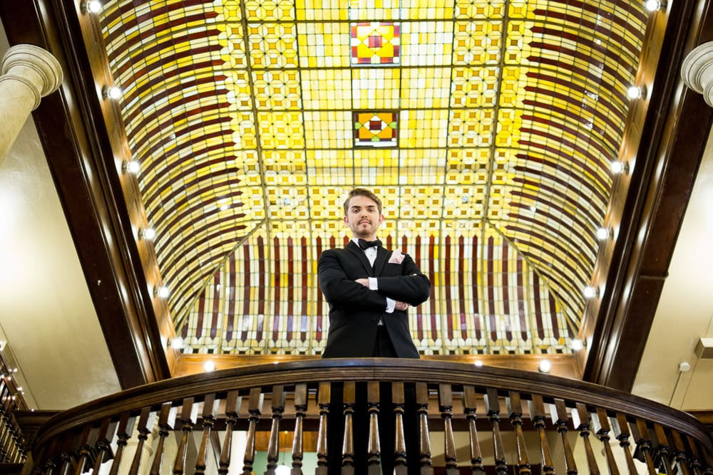 A groom stands on the balcony of the Hotel Boulderado before his vintage Boulder wedding.