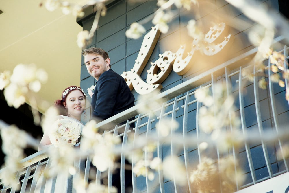 A bride and groom smiling on the balcony of the Rembrandt Yard wedding venue in Boulder, Colorado.