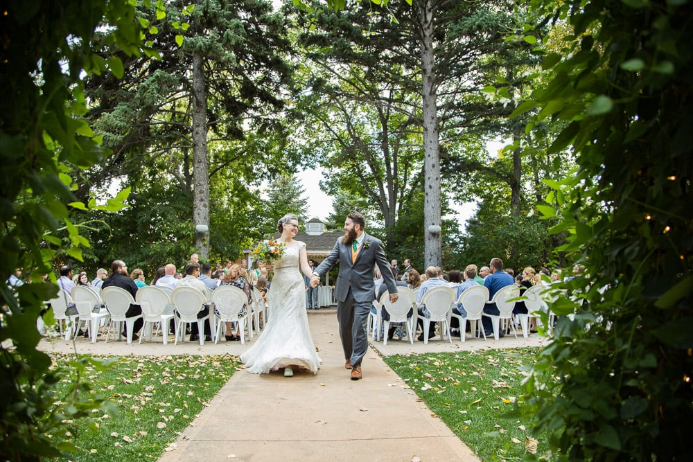 A bride and groom laugh as they walk back down the aisle after their Tapestry House wedding ceremony.