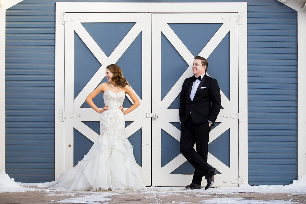 A fun bride and groom laughing in front of a barn door on their snowy wedding day in Old Town Fort Collins.