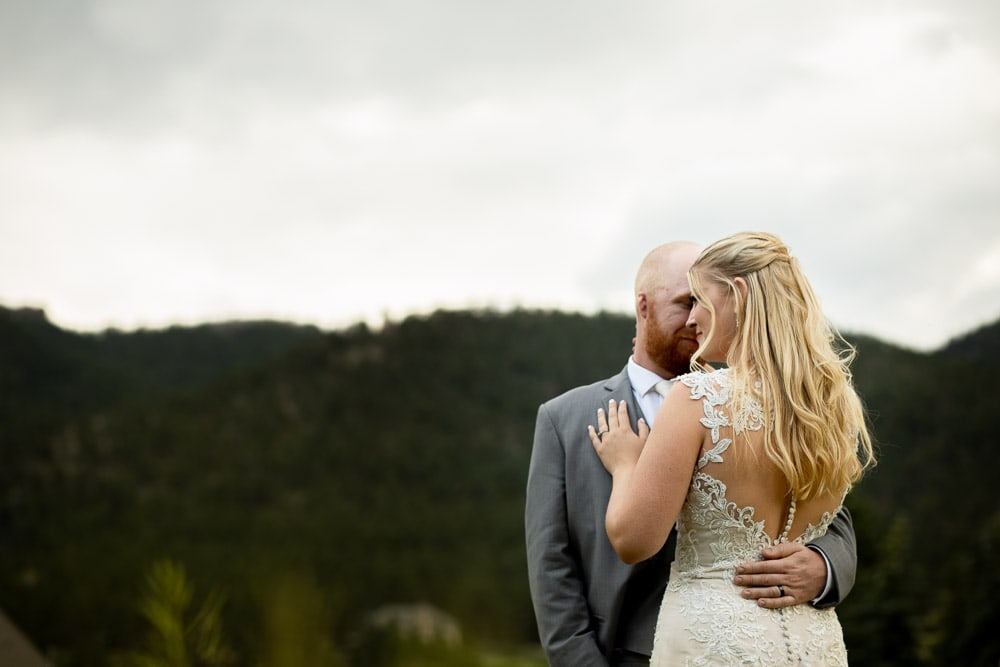 A couple embrace in a field on their wedding day at their rustic Mon Cheri wedding by Colorado Cherry Company.