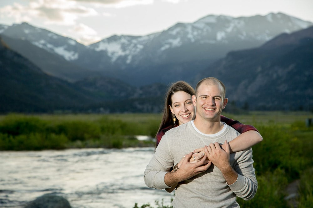 A couple smiling in field near a stream with mountains in the background during their mountain enagement photo session in Rocky Mountain National Park.