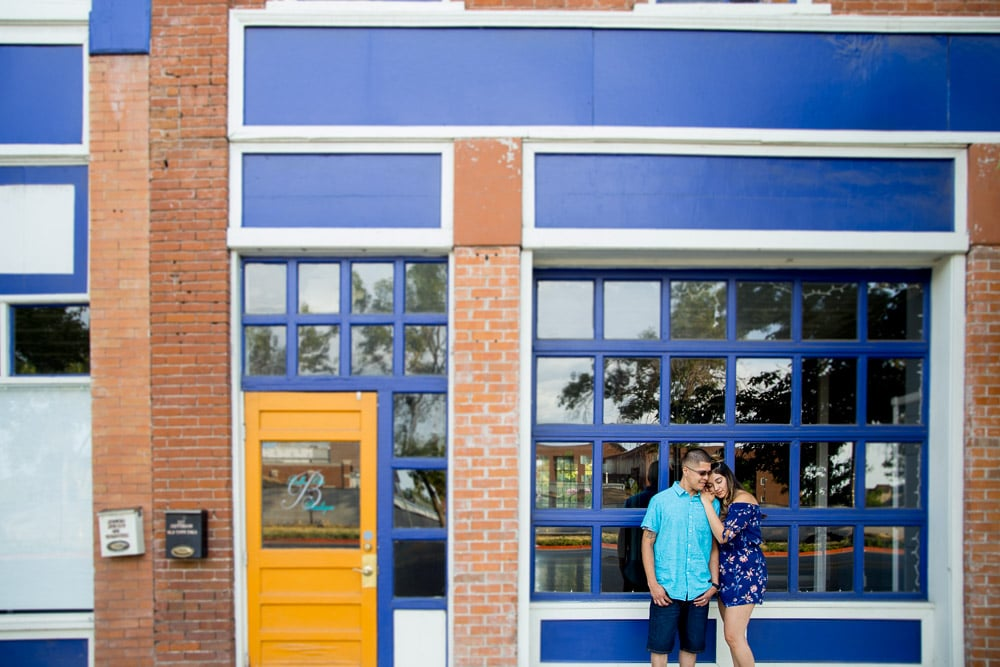 A couple stand in front of brightly colored doors during their urban engagement photo session in Old Town Fort Collins.