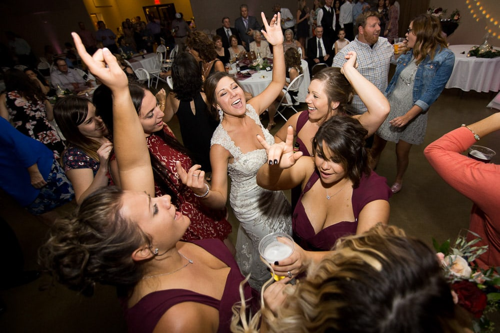 A bride singing on the dance floor with her bridesmaids at her Longmeadow Event Center wedding