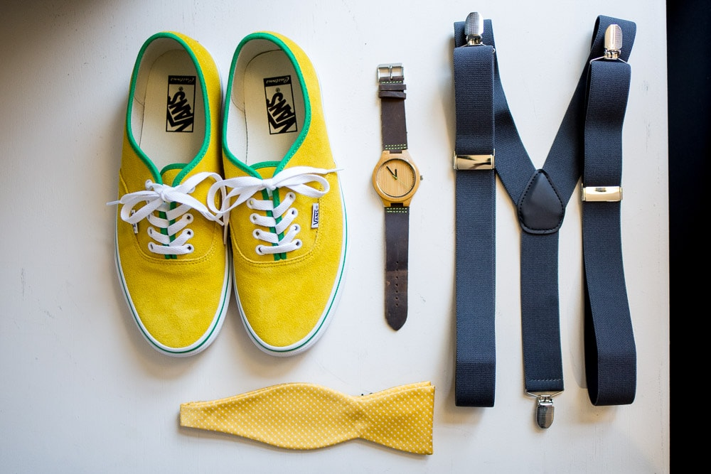 A grooms shoes, tie, suspenders and watch sit arranged on a table at his WEdgewood Boulder Creek wedding.