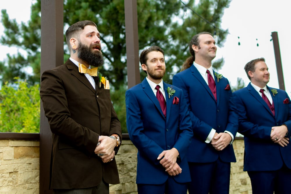 A groom cries as he sees his bride walk down the aisle at their Wedgewood Brittany Hill wedding in Denver, Colorado.