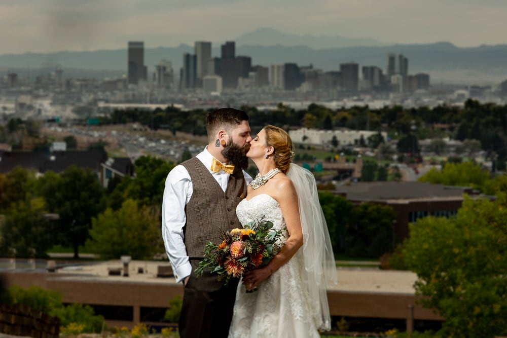A bride and groom kiss with the Denver skyline in the background after their modern wedding at Wedgewood Brittany Hill.