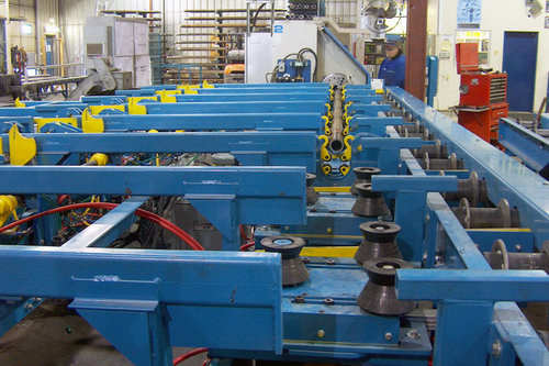 Powered feed conveyor to a CNC turning center. Feed features V pinch rollers and steady rests to support the pipe while being threaded.