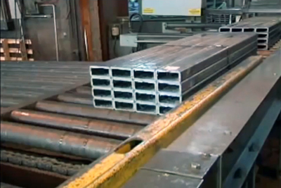 Conveyor Video thumbnail. Bundle of saw cut steel tubing staged on a roller conveyor outfeed.