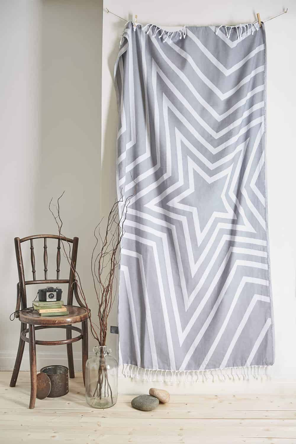 Studio product photograph naturally lit showing a throw hung and styled with vintage props