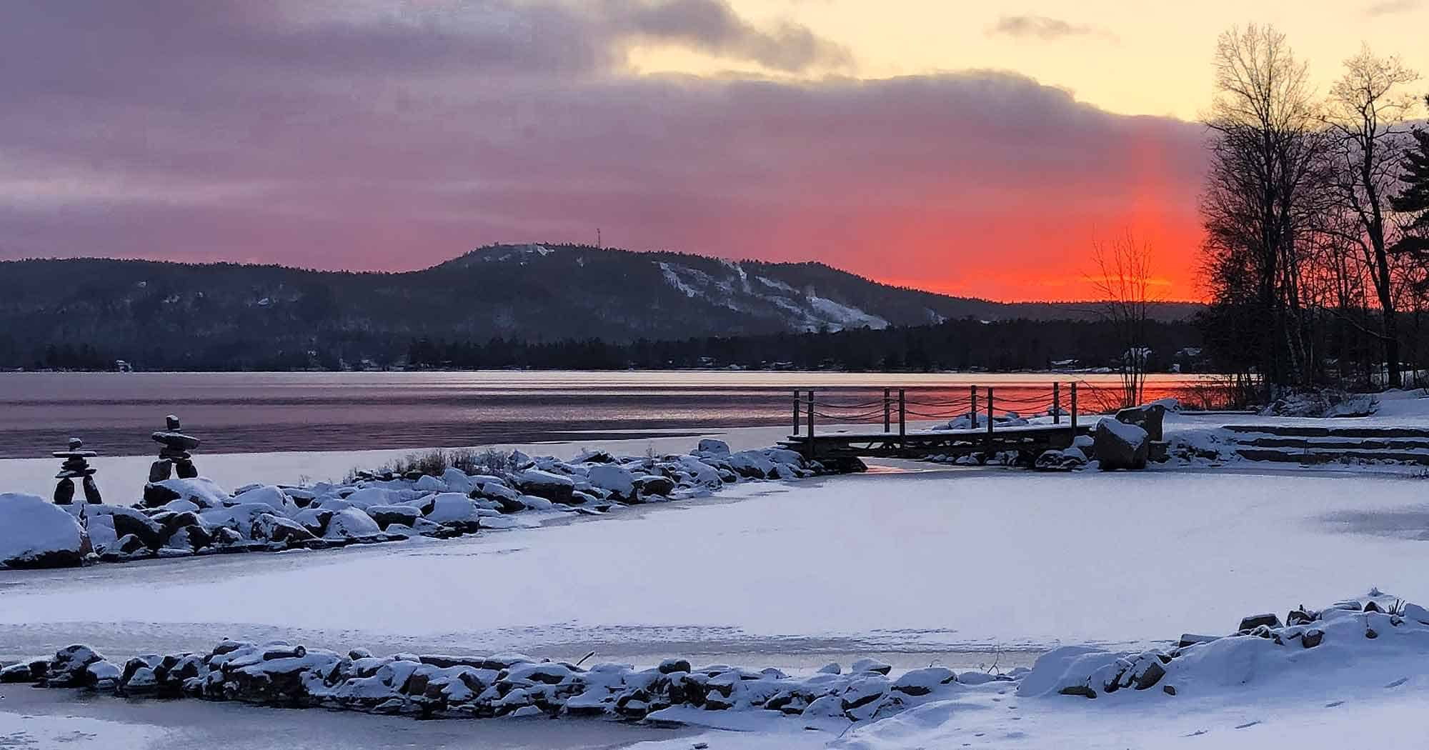 Beach area in winter with sunset over Dickson Mountain