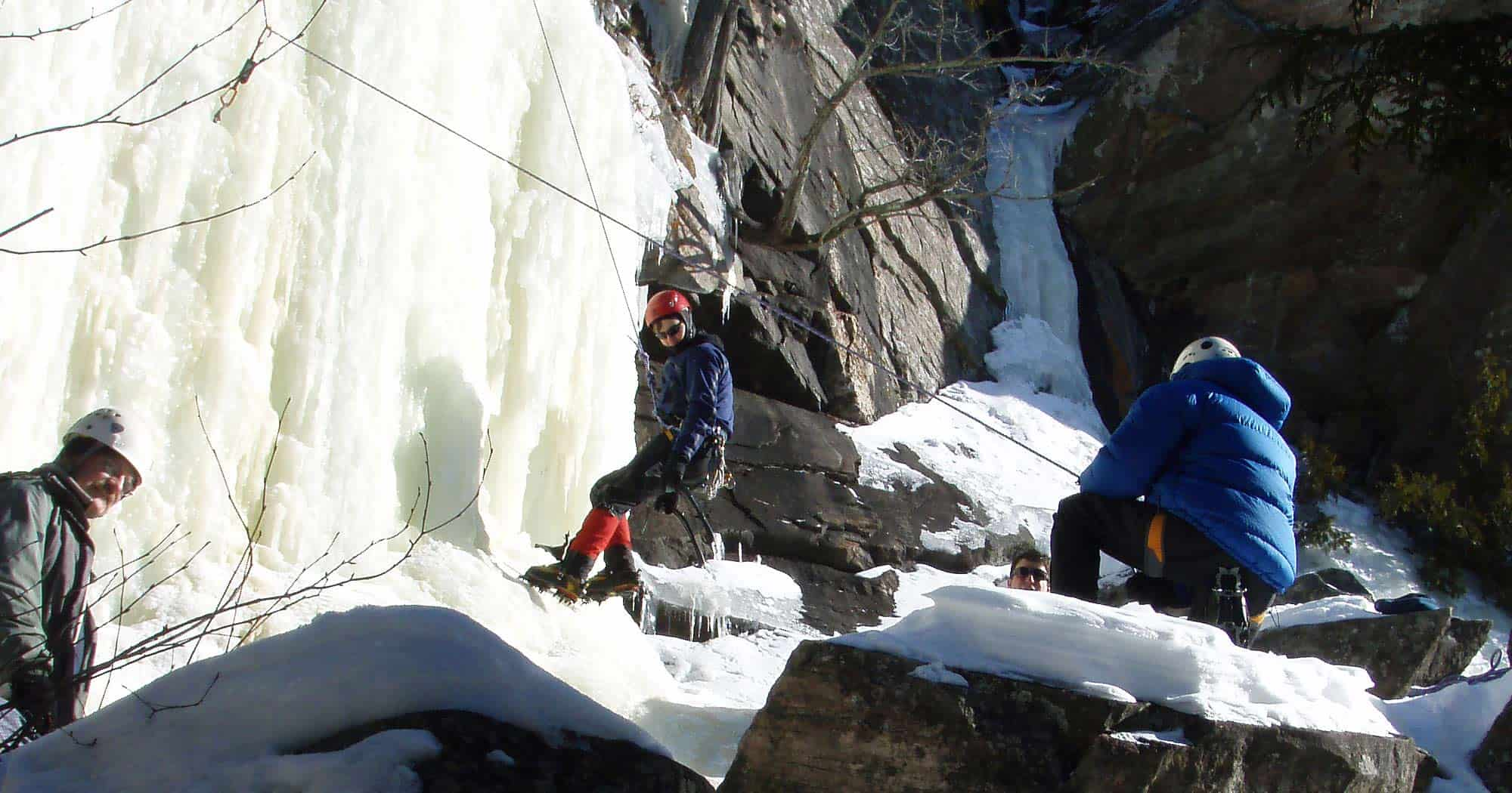Three ice climbers at the base of a cliff