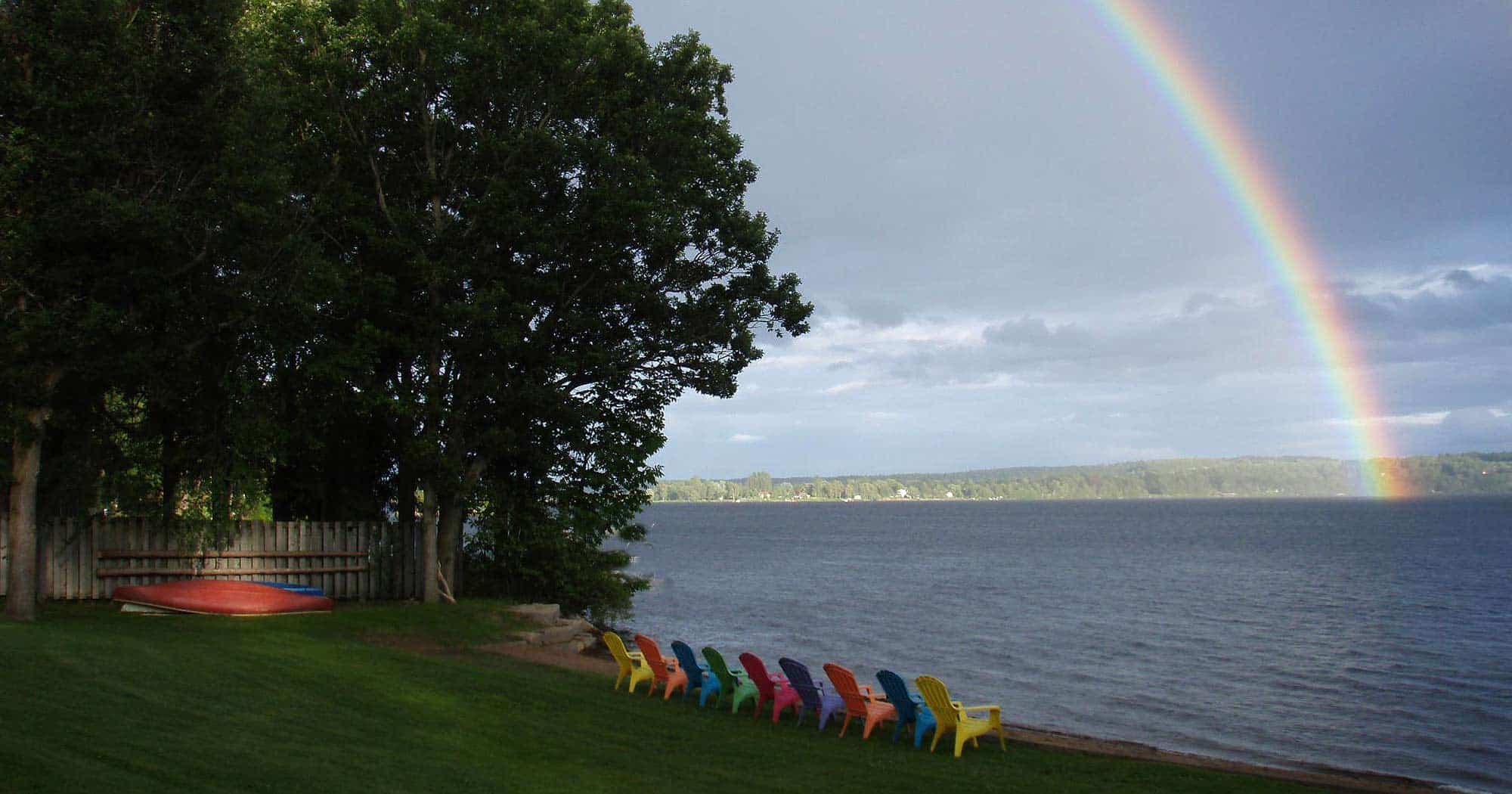 View of Calabogie Lake with colourful chairs at the water;s edge and a rainbow.